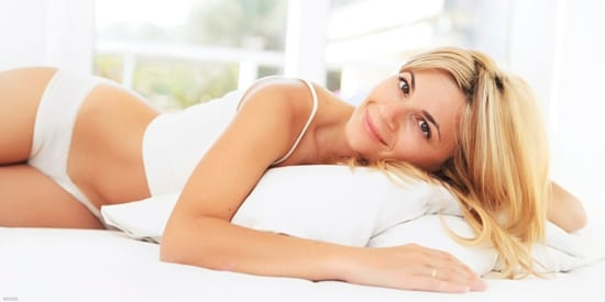 Beautiful woman in white tank and briefs lying on a bed smiling
