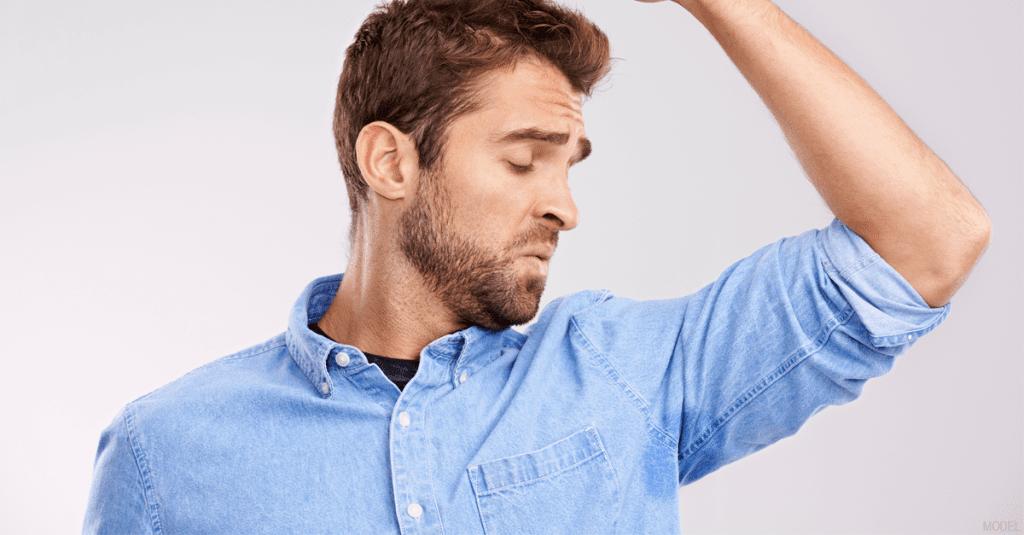 Man smelling his underarm