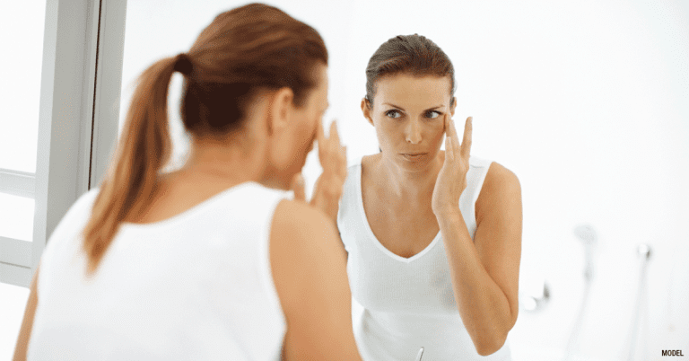 Woman with ponytail looking in mirror and applying cream