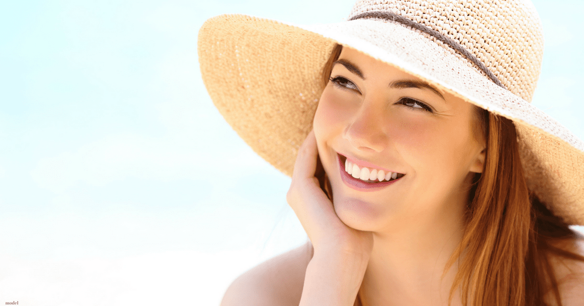 Young woman smiling in sun hat
