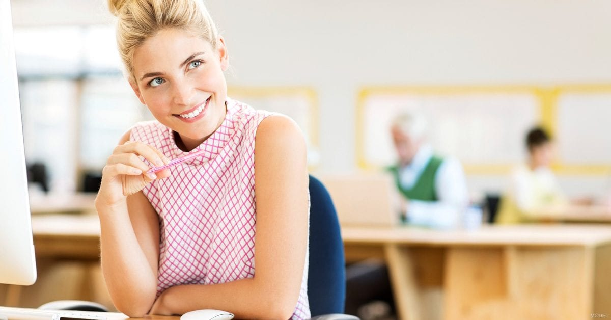 Woman at desk in office considering what to do on her lunch break
