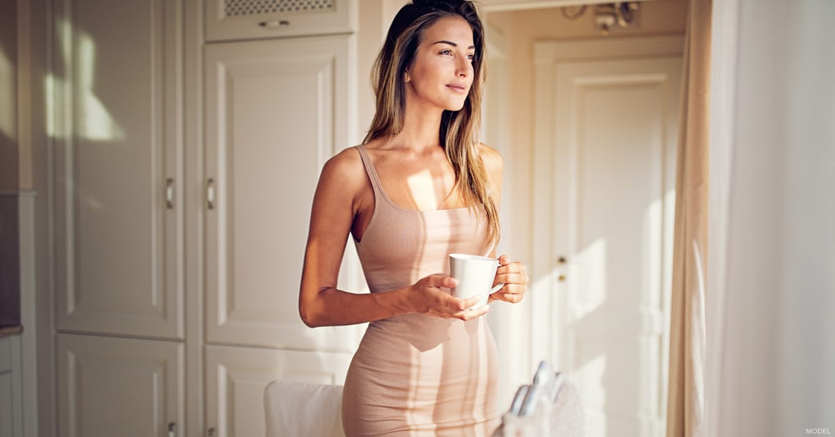 Woman holding coffee looking out window considering body contouring options in Dallas, Texas