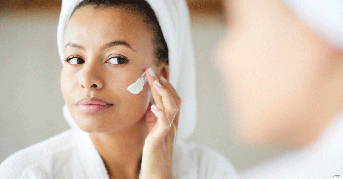 Woman in Dallas, TX applying skincare product recommended by her dermatologist