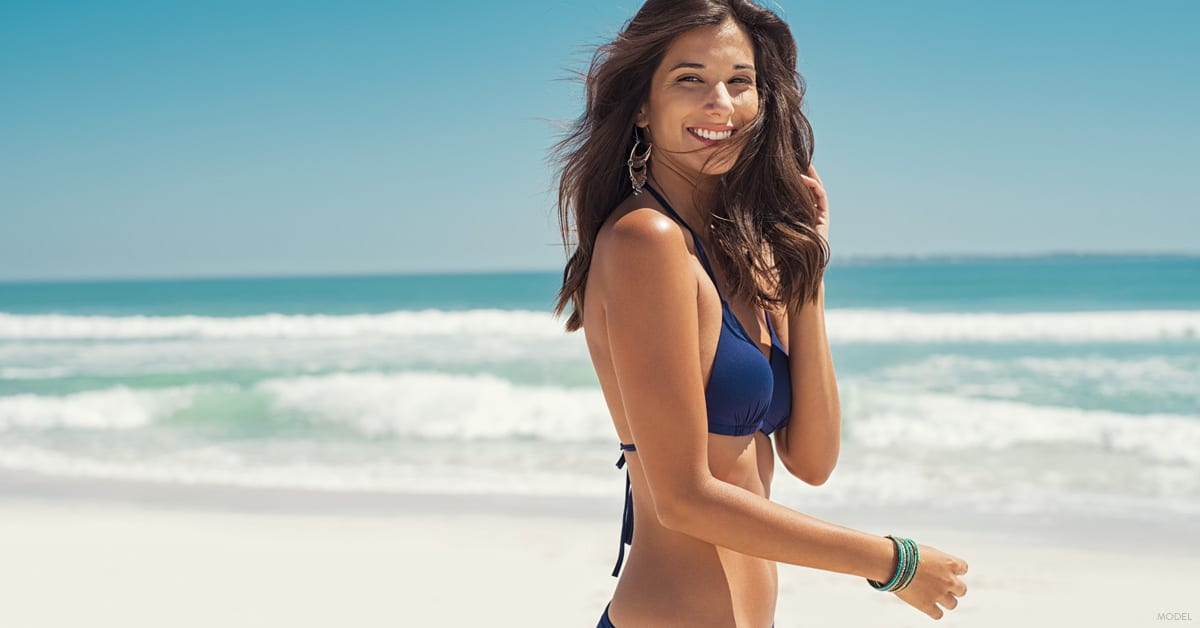 Woman with great body smiling on the beach